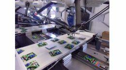 Zwei Deltaroboter greifen die Teile und kleben sie mit einem Druckluftimpuls auf die vorbeilaufenden Zeitschriften.