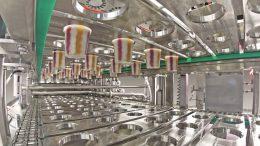 Blick in die vierbahnige Längsläufer-Becherfüllanlage FOODLINER 6.000 für die Abfüllung von fruchtunterlegten und geswirlten Milchprodukten.