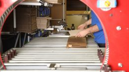 Die TL-Wickelanlage formt aus einer flach liegenden Wellpappe und einer elastischen Folie eine polsternde sowie fixierende Schutzverpackung.