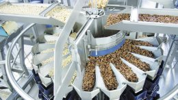 Unterschiedliche Nusssorten und sehr klebrige Trockenfrüchte werden verwogen und verpackt.