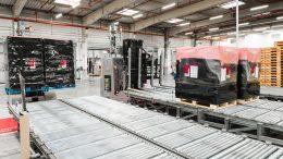 Automatisierte Transportfahrzeuge platzieren jeweils zwei Paletten auf den Schwerlast-Schwerkraftförderern.