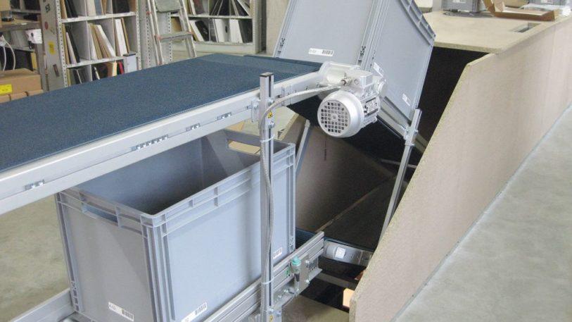 Steigförderband zum Transport der Kommissionierboxen über zwei Etagen hinweg