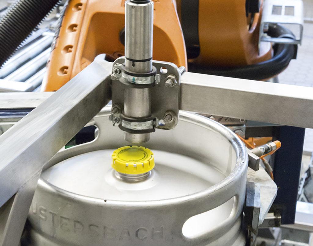Ein Roboterarm führt die zu kennzeichnenden Gebinde zum Linx-Schreibkopf. So muss beim Wechsel auf andere Gebinde der Kopf nicht umgestellt werden. (Bild: Bluhm Systeme GmbH)