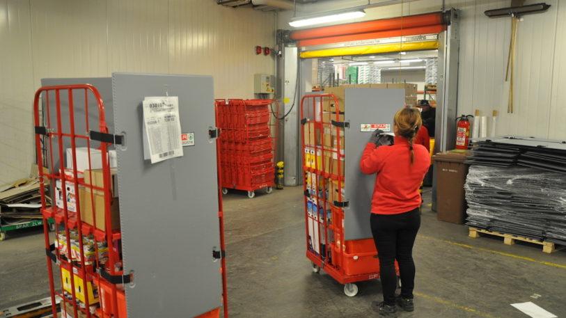 Eine Spar-Mitarbeiterin kommissioniert einen Roll-Safe-Container in einem österreichischen Spar-Lager. (Bild:Press'n'Relations und SPAR)