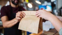 Mann reicht Take-away Papiertüte über Tresen