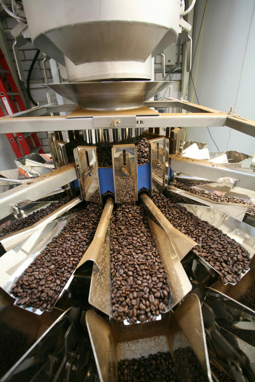 Die Kaffeebohnen gelangen durch einen Trichter auf die Mehrkopfwaage und werden über einzeln ansteuerbare Radialrinnen gleichmäßig auf die Vorschalen der Waage verteilt. (Bild: Ishida)