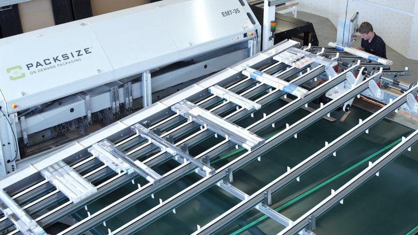 Die Komplettlösung von Packsize und Becker verpackt lose Produkte zu versandfertigen Kartons. Während die EM 7 Kartons bedarfsgerecht und passgenau zuschneidet, transportiert ein maßgeschneidertes Produktförderband die Bestellpositionen zum Packplatz. (Bild: Packsize GmbH)