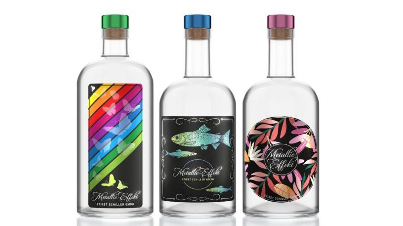 Drei Spirituosenflaschen mit bunten Etiketten im Metallic Look