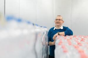 Eine Person steht zwischen Getränkeflaschen aus Kunststoff