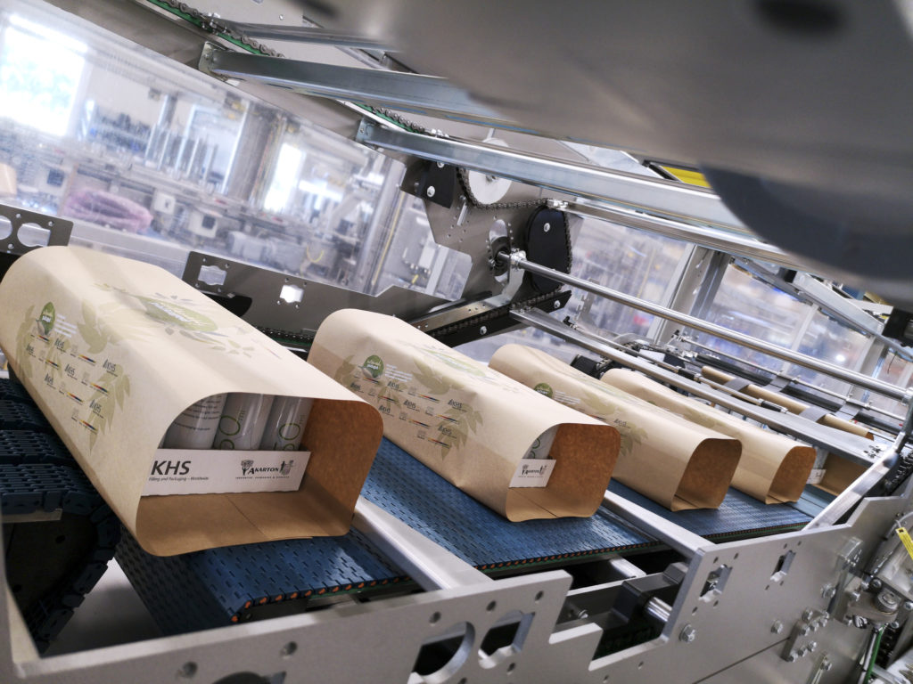 Ein Traypacker schlägt Dosentrays in Papier ein