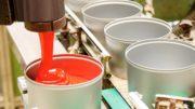 Eine Weißblechdose wird maschinell mit roter Farbe gefüllt