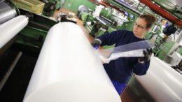 Eine Auszubildende schneidet ein Stück Folie von einer Folienrolle