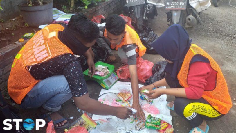 Drei Menschen sortieren für Projekt STOP in Indonesien Verpackungsmüll aus Plastik