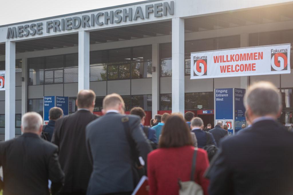 Besucher auf dem Weg zur Messe Fakuma in Friedrichshafen