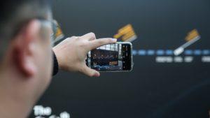 Mann hält Smartphone und filmt auf der Veranstaltung SPS