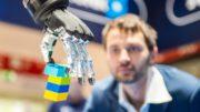 Hand eines Industrieroboters greift Bausteine aus Kunststoff
