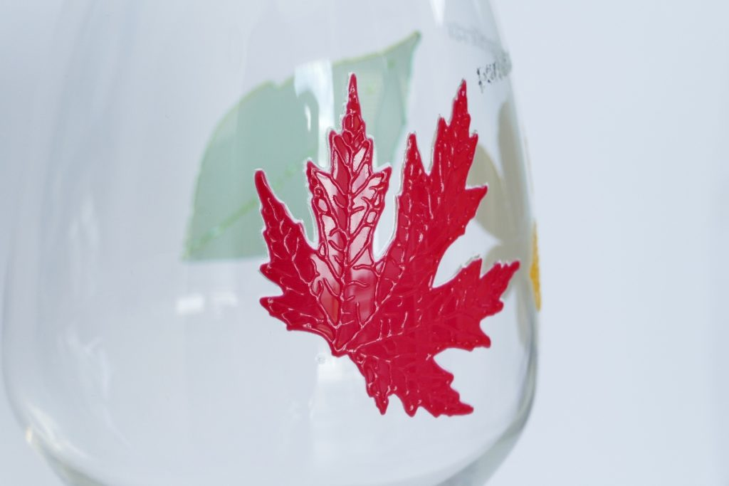 Detailbild eines rotfarbigen Blatts mit haptischen Effekt auf einer durchsichtigen Glasflasche