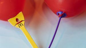 Zwei rote Luftballons, die mit Papierhaltern versehen sind. Der linke ist gelb und trägt das Logo von McDonald's