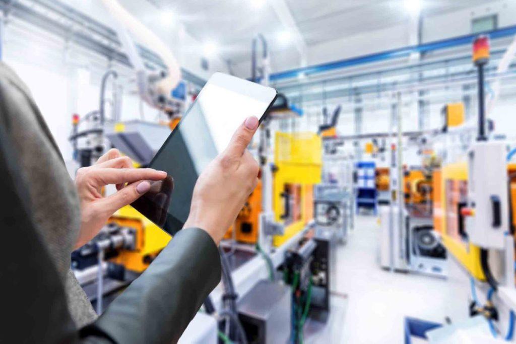 Cloud-Lösung: Im Vordergrund wird ein Tablet gehalten, mit dem die Produktionsprozesse im Hintergrund gesteuert werden.