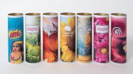 Sieben Dosen ohne Deckel demonstrieren die Bedruckung von Hohlkörpern mit unterschiedlichen Motiven