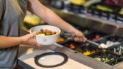 Eine Kunststoffschale wird an der Salatbar befuellt.