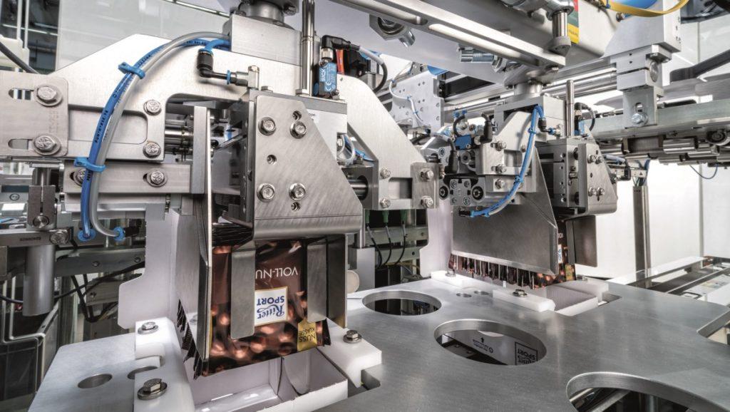 Ein Roboter übernimmt eine Schokoladentafel von Ritter Sport und setzt sie auf den Kopf gestellt in den Deckel des Kartons ein.