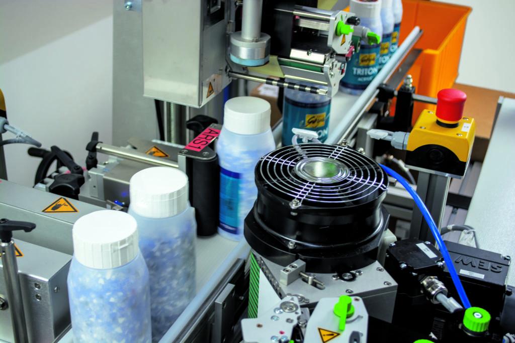 Etikettierer bringt Etiketten auf Kunststofftiegel