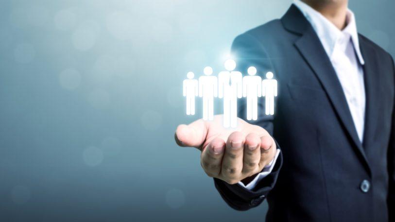 sinnbildlich fuer Personal Recruiting präsentiert eine Mann im Anzug fünf menschliche Gestalten in seiner geoeffneten Handsnchlcihe
