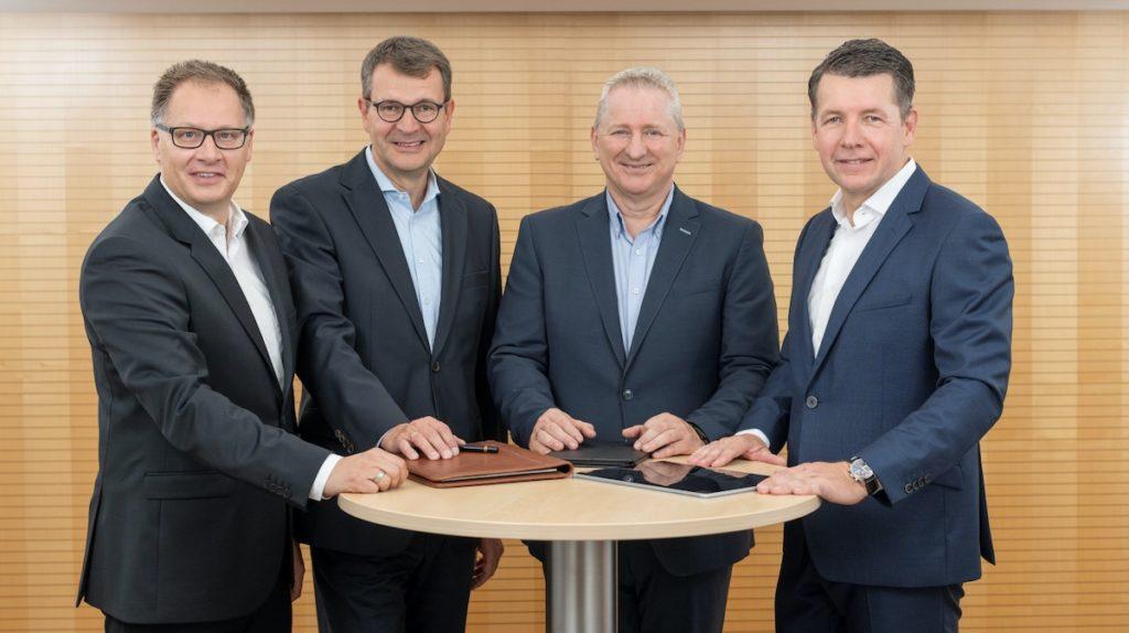 Die vier Geschäftsführer des Unternehmens Packservice stehen an einem runden Tisch.