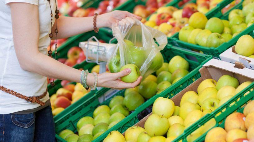 eine Frau packt Obst in Plastikbeutel