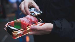 Sushi To-go-Verpackung in den Händen eines Mannes