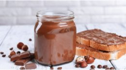 Nutella-Glas mit Brot und Schokolade und Nüssen