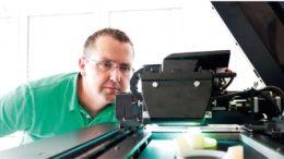 Mann schaut auf einen 3D-Drucker