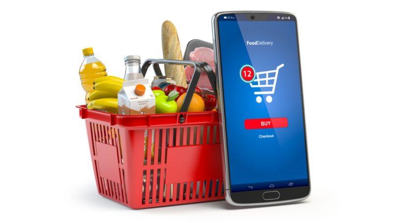 Einkaufkorb mit Waren und Smartphone