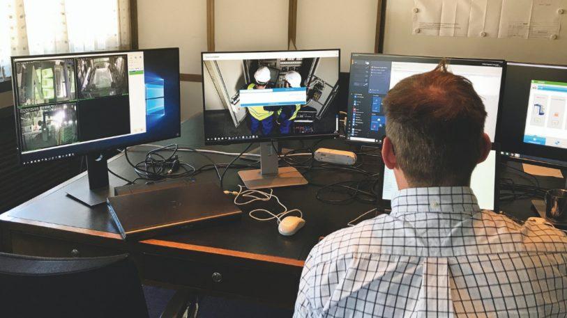 Mann vor mehreren Bildschirmen überwacht Inbetriebnahme aus der Ferne