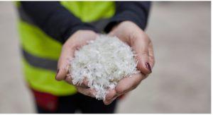 Frau hält recycelten Kunststoff in den Händen