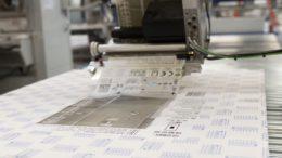 Die großen Design-Etiketten mit Informationen zum Produkt und Prüfsiegeln appliziert ein Etikettenspender Alpha HSM.