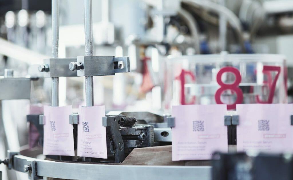Kleine Siegelrandbeutel mit Hautcremeproben werden auf einer Rundläufermaschine gefertigt.