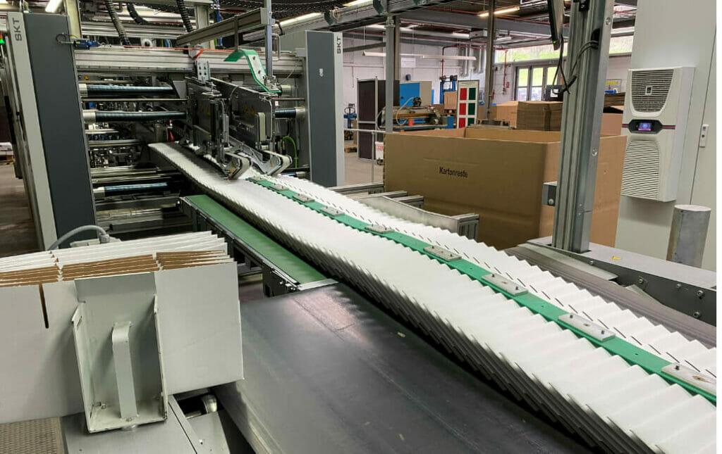 Der Schuppenstrom aus der Faltschachtelklebemaschine wird über ein Pressband vollautomatisch zum Powerpacker geführt.