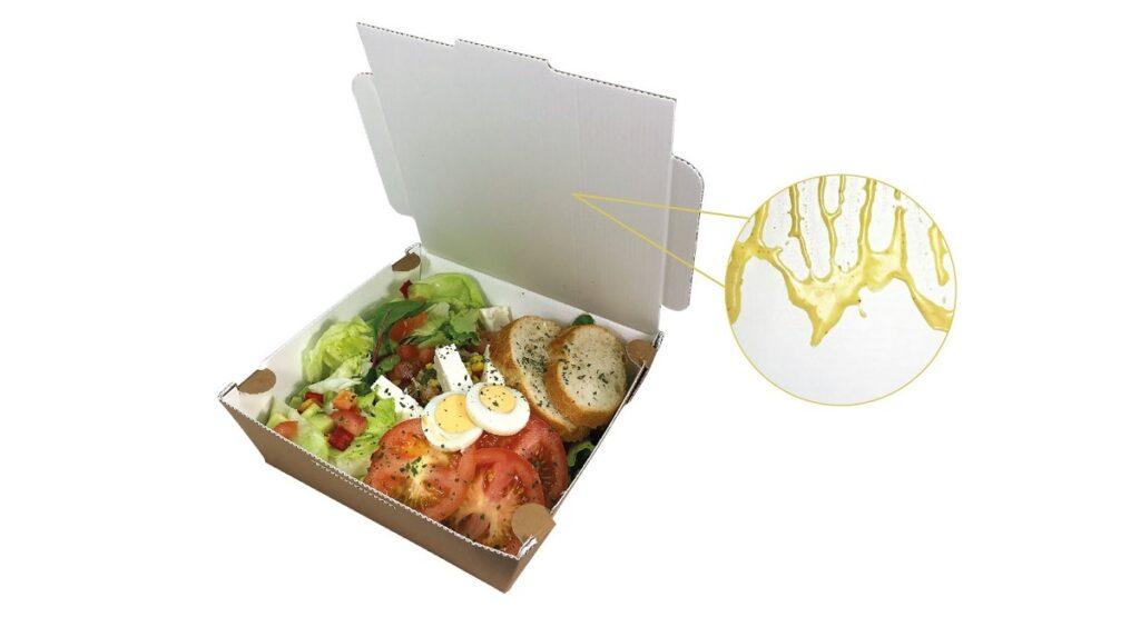Die Salat-Menüschale besteht aus dem neuen beschichteten Papier ComBa Liner von Thimm. Am Beispiel der Salatsoße zeigt sich der Abperleffekt