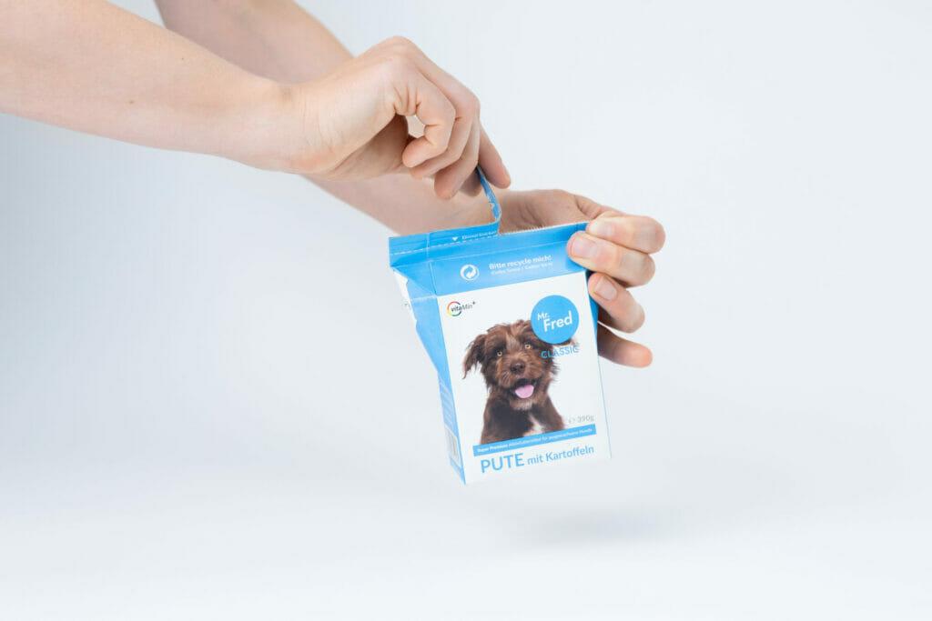 Eine Hand hält das Tetra Pak mit Mr. Fred Hundefutter und eine die andere Hand reist den Verschluss auf.