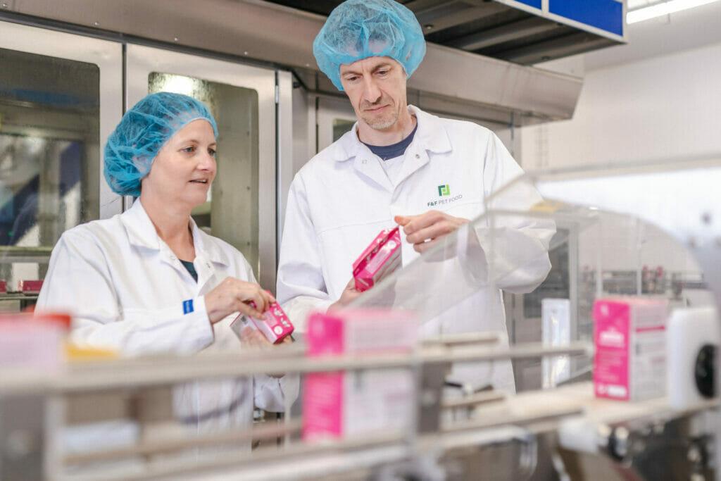 Die Gründer Beate Rank und Tobias Kobier stehen in der Produktion und halten die fertigen Produkte in der Hand.