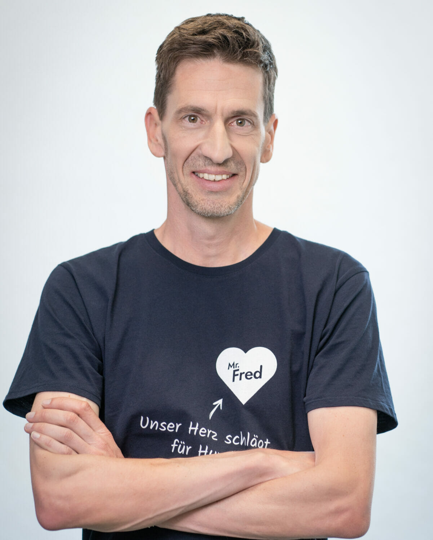 Gründer Tobias Kobier steht lächelnd mit verschränkten Armen.