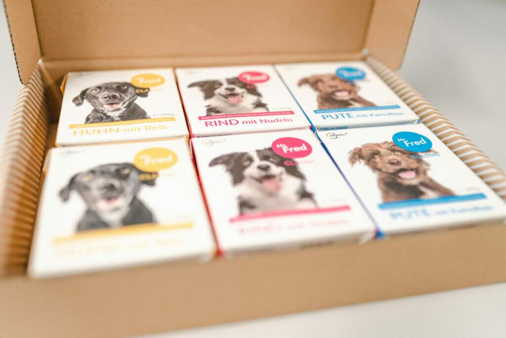 Karton mit sechs Packungen Hundefutter. Die Tetra Paks von Mr. Fred sind gelb, blau und pink und zeigen einen Hund.